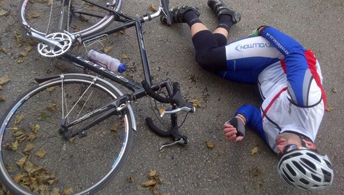 kolesar leži na tleh z mišičnim krčem v zadnji loži stegna