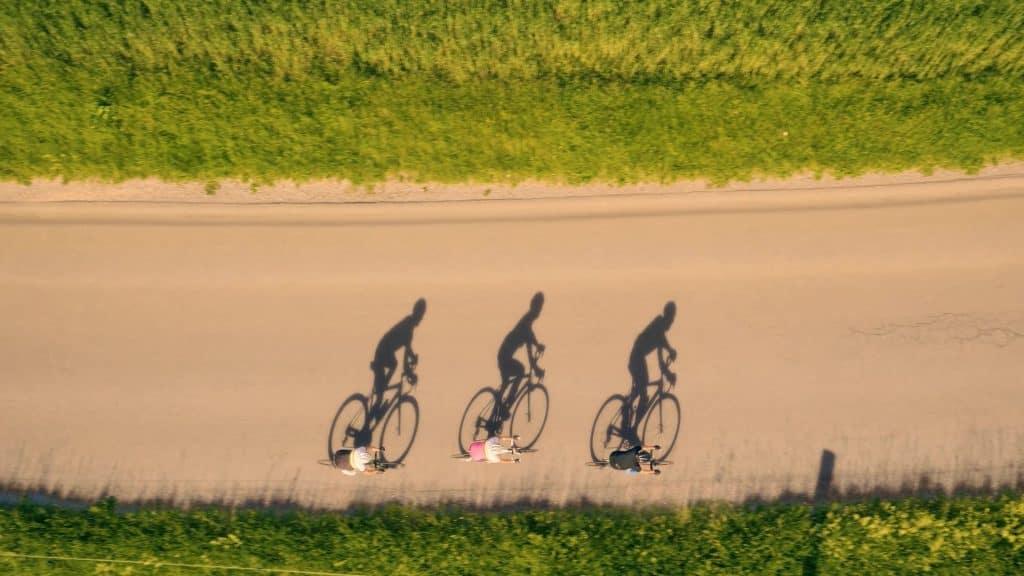 Kolesarji v skupini. Vožnja v zavetrju. Drone posnetek iz zraka.