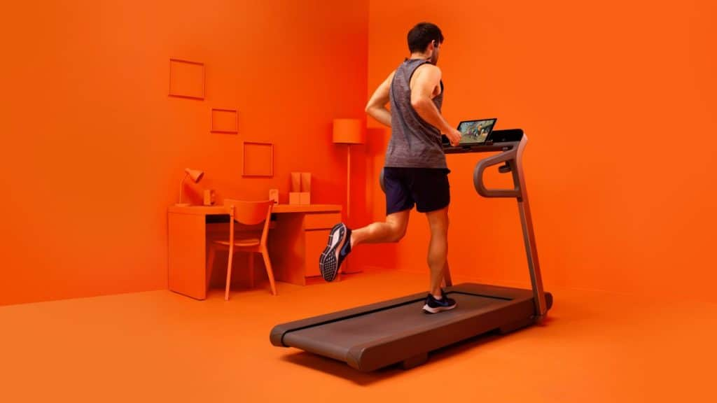 Tekač na tekaški stezi uporablja ZWIFT virtualno platformo.